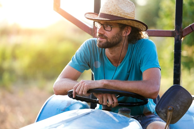 Foto do agricultor jovem hippie no trator, procurando sua colheita no jardim.
