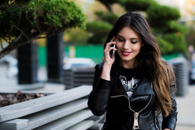 Foto do aluno falando ao telefone ao ar livre