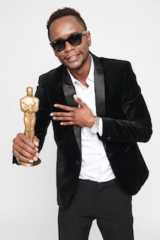 Foto do atraente empresário africano de óculos segurando o prêmio oscar. isolado sobre fundo branco. olhe para a câmera.