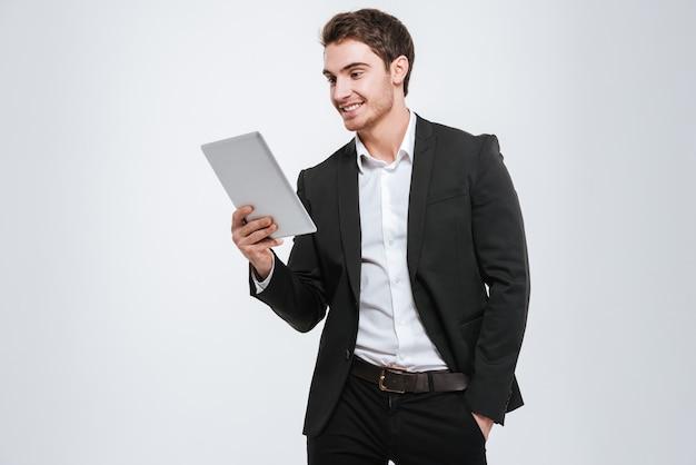 Foto do atraente jovem empresário caucasiano em pé. isolado sobre a parede branca. olhe para o lado e segure o computador tablet nas mãos.