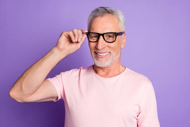 Foto do avô aposentado segurando óculos sorrindo, usando óculos, camiseta rosa isolado fundo de cor violeta
