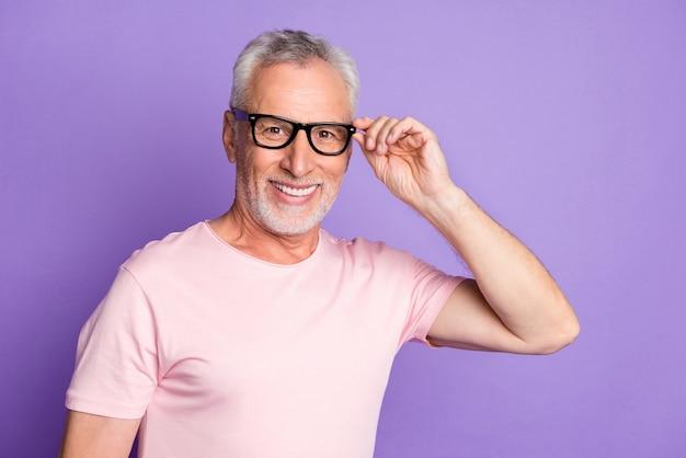 Foto do avô aposentado segurar especificações olhar câmera sorrindo usar óculos t-shirt rosa isolado fundo de cor roxa