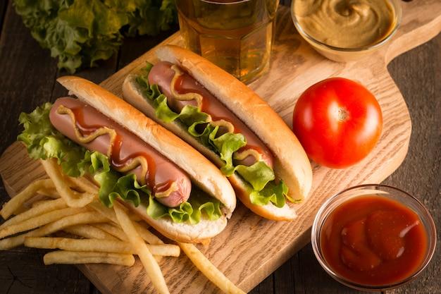Foto do cachorro quente grelhado assado com mostarda amarela e ketchup em de madeira. sanduíche de cachorro-quente com batatas fritas e molhos.