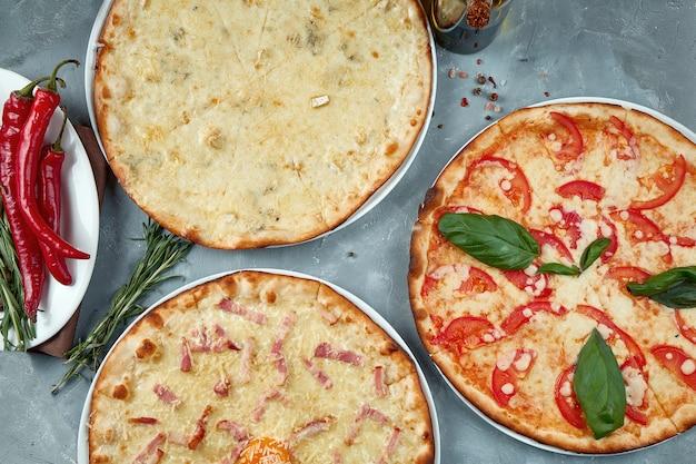 Foto do cardápio da pizzaria. três pizzas diferentes, margarita, quatro queijos e bacon .. vista superior. cama plana de alimentos