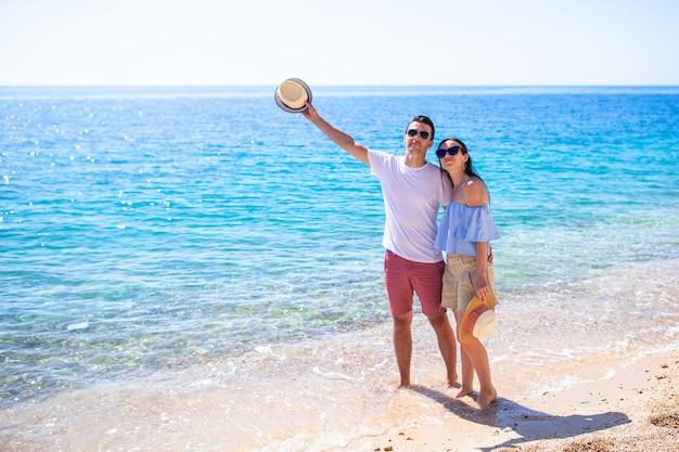Foto do casal feliz em óculos de sol na praia