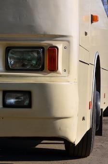 Foto do casco de um grande e longo ônibus amarelo.