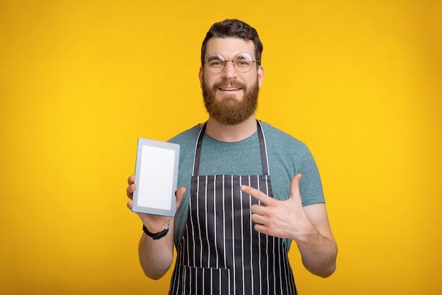 Foto do chef alegre homem em cima de amarelo e apontando para o tablet de tela