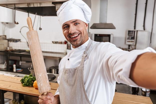 Foto do chefe de um homem bonito de avental tirando uma selfie, em pé na cozinha em um restaurante