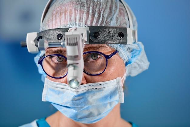 Foto do cirurgião operacional na sala de cirurgia. cirurgião em máscara e óculos com farol montado. fechar retrato