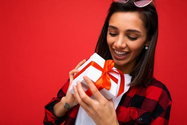 Foto do close up da bela jovem morena feliz isolada na parede de fundo vermelho