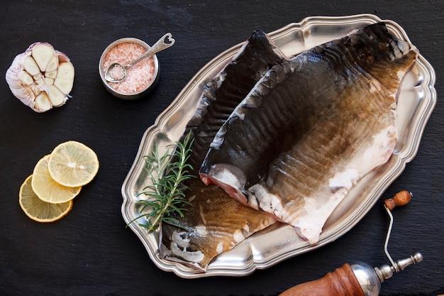 Foto do close-up da faixa de peixes crus fresca com sal e limão do mar no fundo preto da tabela concreted.