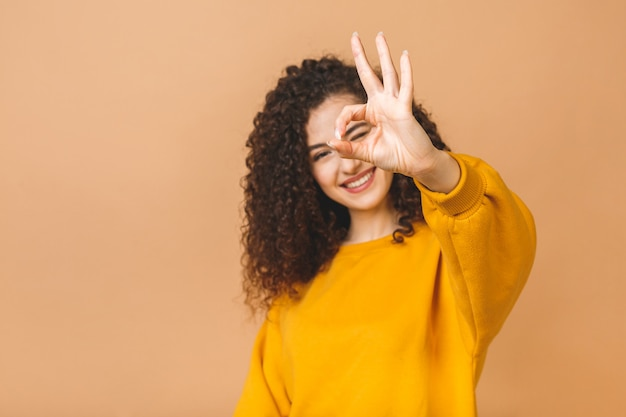 Foto do close-up da mulher moreno nova encaracolado engraçada no gesto aprovado mostrando ocasional, olhando a câmera, isolada no fundo bege.