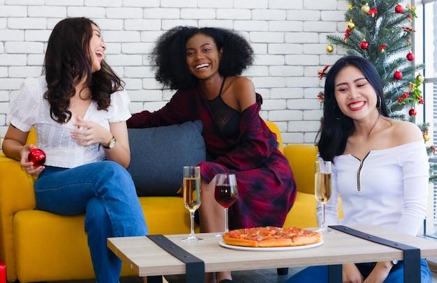 Foto do close up das meninas alegres que comemoram um partido em casa com campanha e pizza.