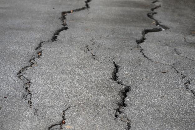 Foto do close up de asfalto rachado na estrada ou na rua local após o terremoto ou o el nino.