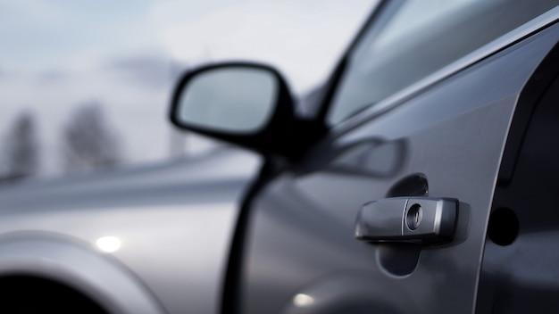 Foto do close up de uma maçaneta prateada escura de carro