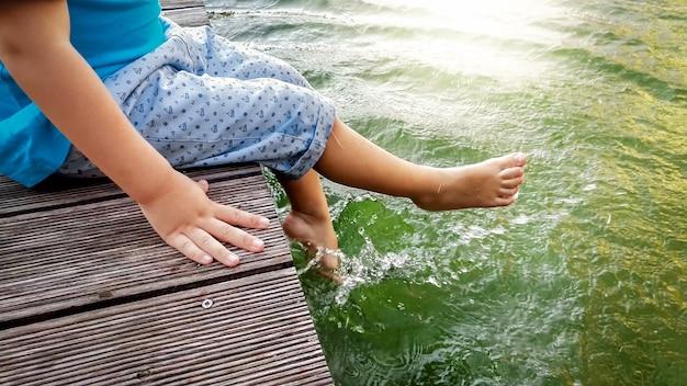 Foto do close up do garotinho de 3 anos sentado no cais de madeira e segurando os pés na água do rio. criança brincando no lago com as pernas