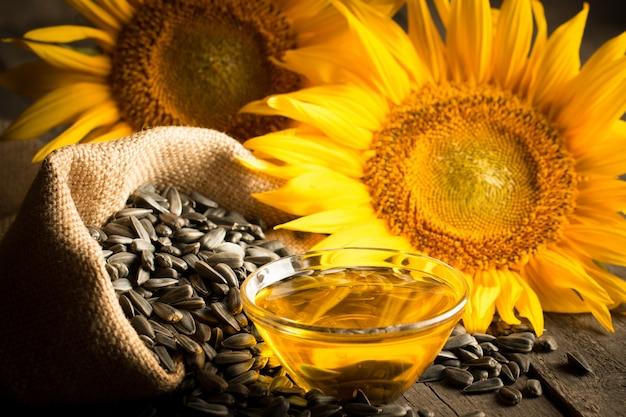 Foto do close up do óleo de girassol com as sementes no fundo de madeira. conceito de produto bio e orgânico.