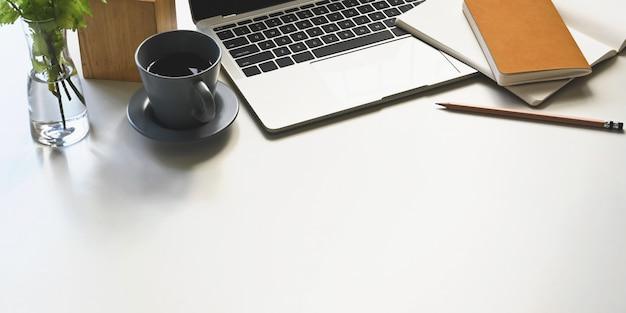 Foto do computador portátil, xícara de café, caderno, diário, lápis, porta lápis, planta em vaso, colocando sobre a mesa de trabalho branca. conceito de local de trabalho em ordem.