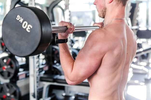 Foto do conceito de esporte, musculação, estilo de vida e pessoas - jovem com uma barra flexionando os músculos na academia