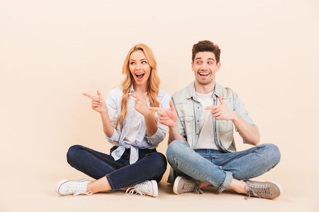 Foto do conteúdo dois amigos, homem e mulher, sentados no chão com as pernas cruzadas e apontando os dedos de lado para copyspace, isolado sobre uma parede bege