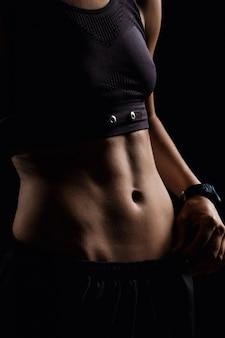Foto do corpo da garota esportiva sobre parede escura.