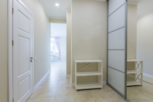 Foto do corredor interno de entrada do apartamento com um grande armário branco