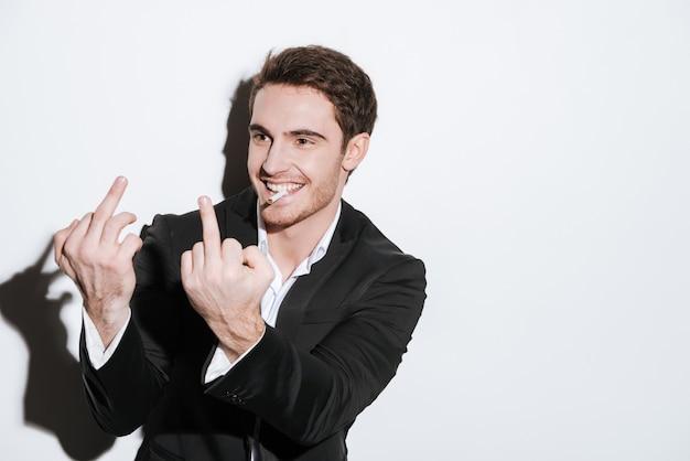 Foto do empresário alegre posando e olhar de lado enquanto segura o cigarro e mostra o dedo médio. isolado sobre a parede branca.
