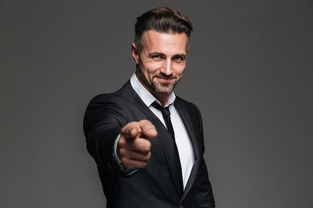 Foto do empresário atraente de terno sorrindo e apontando o dedo indicador, isolado sobre cinza escuro