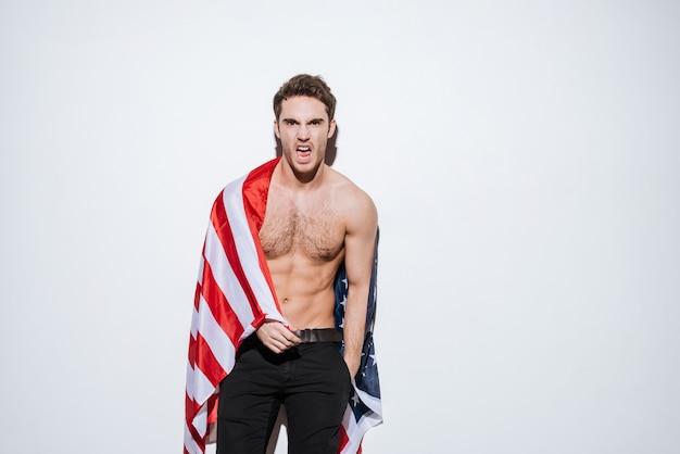 Foto do empresário atraente posando enquanto segura a bandeira dos eua. isolado sobre a parede branca.