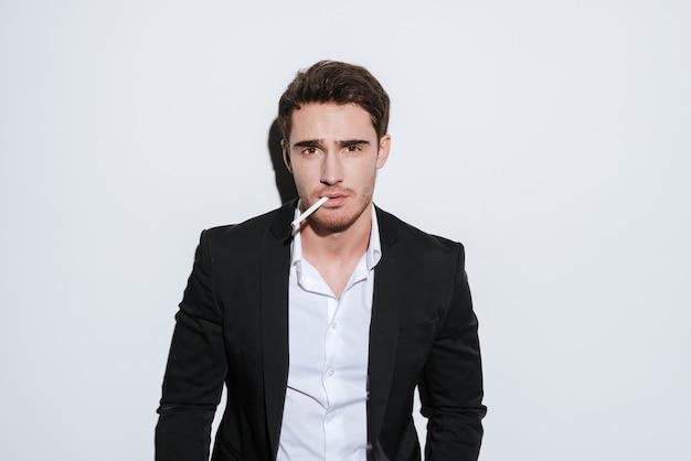Foto do empresário atraente posando enquanto segura o cigarro. isolado sobre a parede branca.