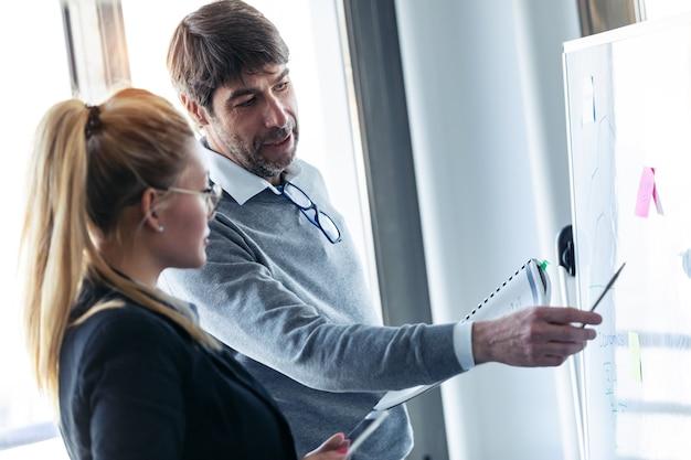 Foto do empresário bonitão apontando para a lousa enquanto explica o projeto para seu colega no local de coworking.