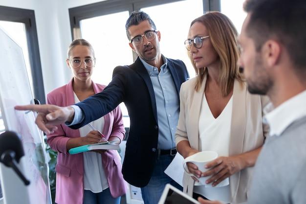 Foto do empresário bonito apontando para uma lousa branca e explicar um projeto para seus colegas no local de coworking.