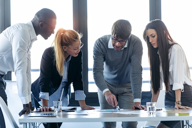 Foto do empresário bonito conversando com colegas na reunião em um espaço de coworking.