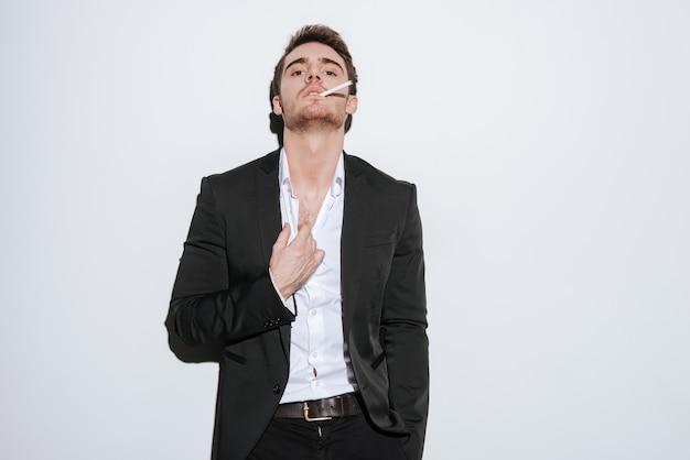 Foto do empresário bonito posando enquanto segura o cigarro. isolado sobre a parede branca.