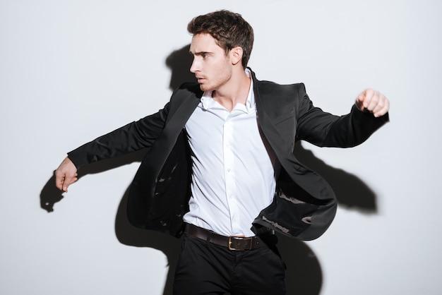Foto do empresário bonito sério em pé e olhar de lado. isolado sobre parede branca