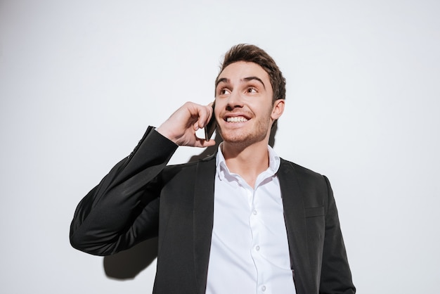 Foto do empresário feliz posando e olhar de lado enquanto fala ao telefone. isolado sobre a parede branca.