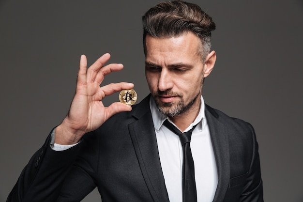 Foto do empresário rico bonito de terno e gravata, olhando para o bitcoin dourado segurando na mão, isolado sobre cinza escuro