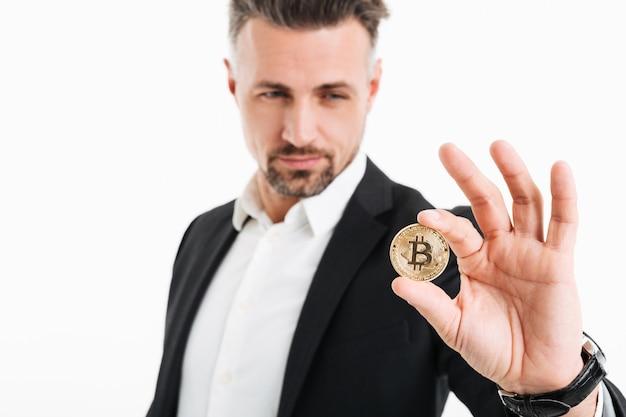 Foto do empresário rico bonito terno mostrando bitcoin dourado focado na câmera, isolada sobre o branco