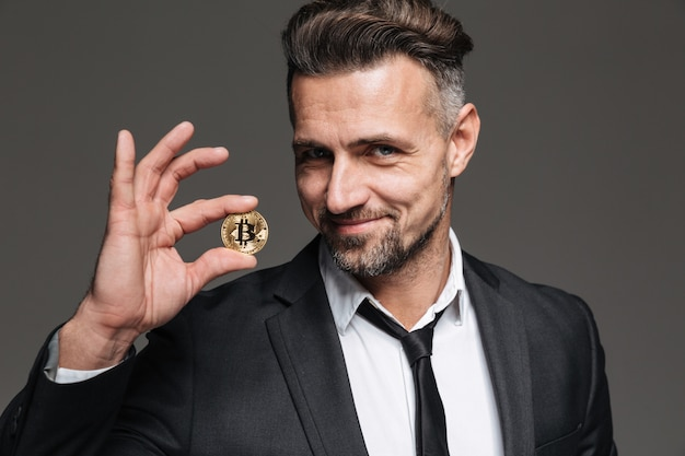 Foto do empresário rico com cabelos castanhos de terno e gravata, sorrindo e mostrando bitcoin dourado na câmera, isolada sobre cinza escuro