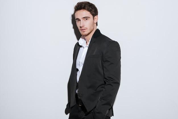 Foto do empresário sério bonito em pé. isolado sobre a parede branca.