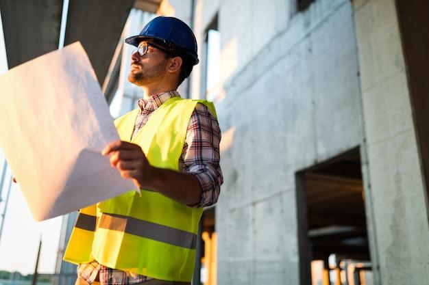 Foto do engenheiro do canteiro de obras olhando para o plano de construção