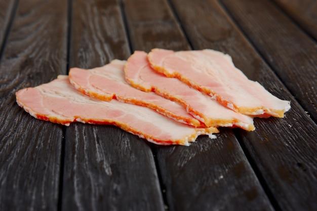 Foto do foco seletivo das fatias de bacon fresco na tabela de madeira.