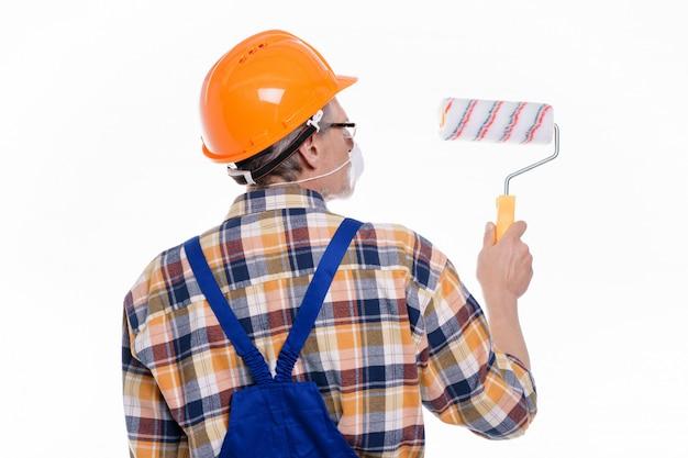 Foto do homem de estucador traseiro em máscara no trabalho com reboco na parede do interior