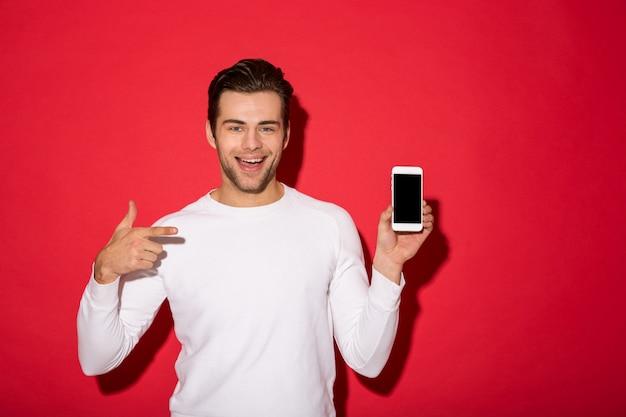 Foto do homem feliz na camisola olhando enquanto segura o smartphone e apontando para ele sobre parede vermelha