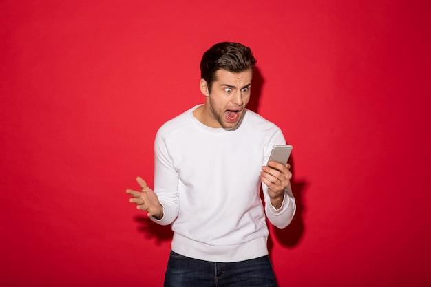 Foto do homem irritado na camisola que grita no smartphone sobre a parede vermelha
