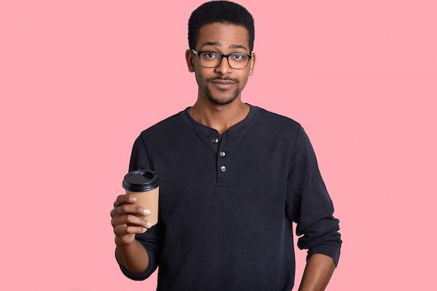 Foto do homem negro bonito com expressão hesitante, tem pele escura, usa óculos, mantém café para viagem