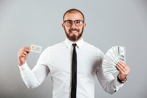 Foto do homem rico 30 anos de óculos e gravata mostrando cartão de crédito e fã de notas de dólar, isoladas sobre parede cinza