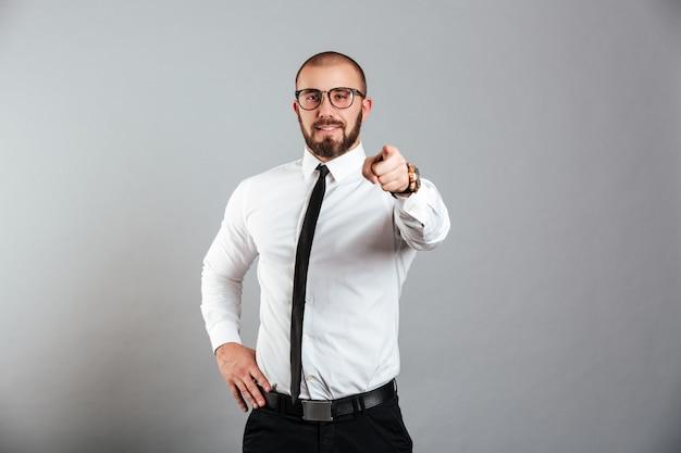 Foto do homem satisfeito do escritório na camisa branca e nos óculos que gesticula no significado do dedo indicador da câmera ei você, isolado sobre a parede cinzenta