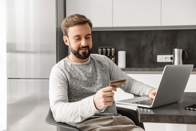 Foto do homem sorridente de 30 anos com roupa casual, sentada sozinha no apartamento e usando o laptop com cartão de crédito para compras on-line