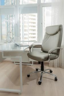 Foto do interior da cadeira de couro do escritório atrás da mesa de trabalho branca